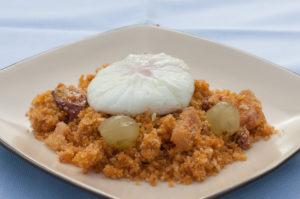 Migas con chorizo, panceta, uva y huevo poché